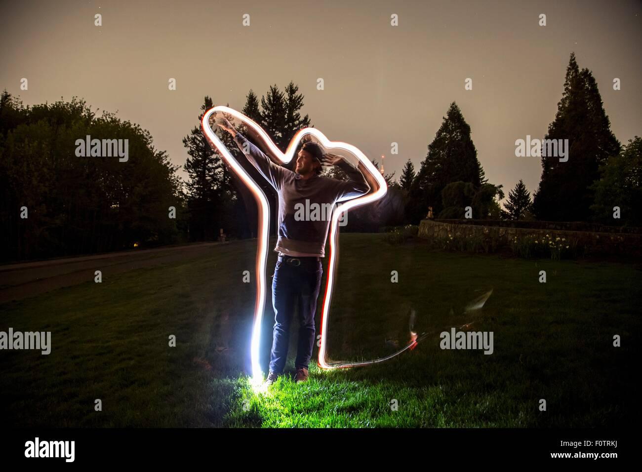 Jeune homme, standing in field, au crépuscule, le bras en position de pointage, sentier lumineux retraçant Photo Stock
