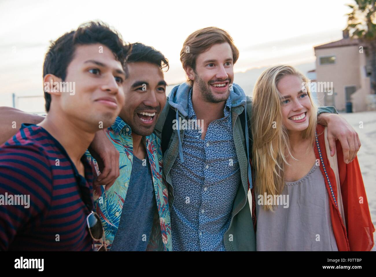 Groupe d'amis Standing together on beach, rire Photo Stock