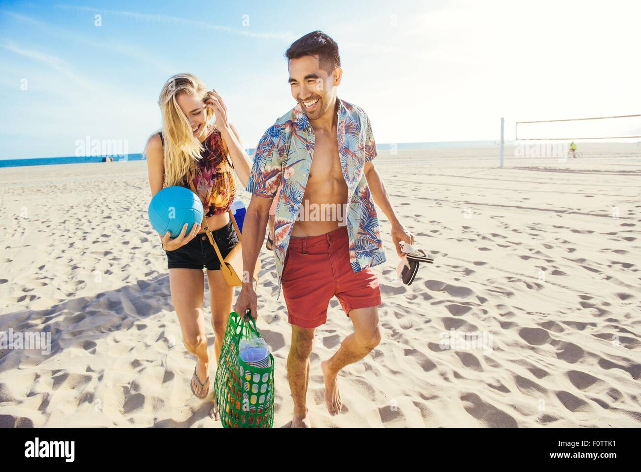 Jeune couple walking on beach, prêt pour un pique-nique Photo Stock