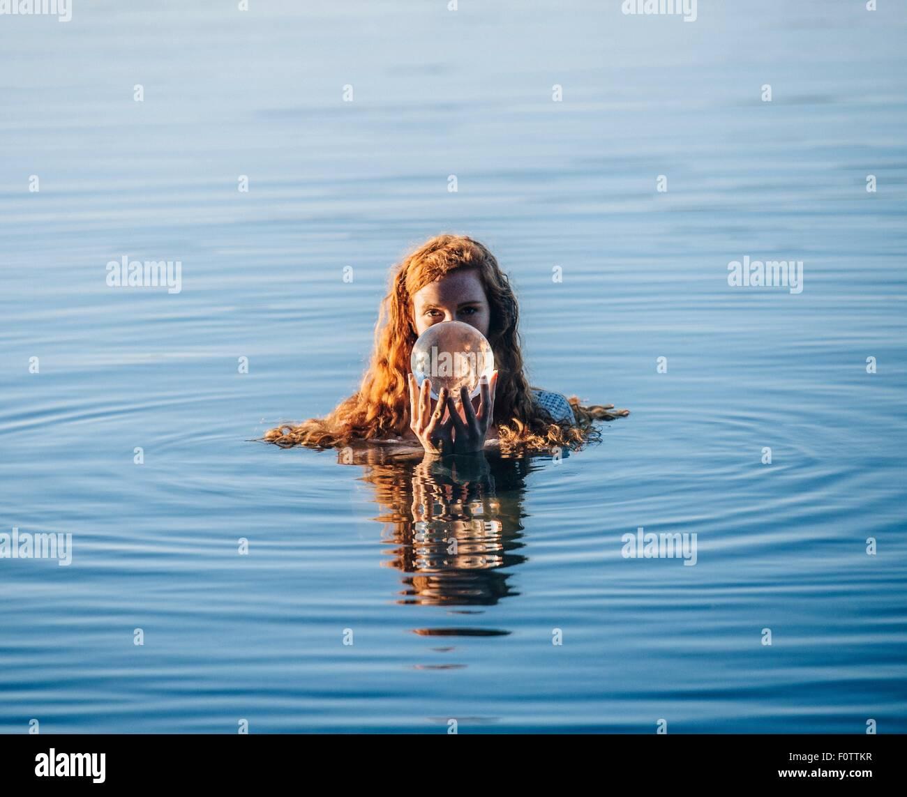 Tête et épaules de jeune femme aux longs cheveux rouges dans le lac holding crystal ball Banque D'Images