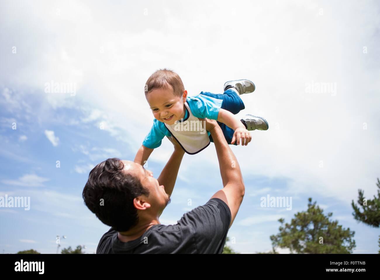 Jeune homme jouant du levage des tout-petit frère dans park Photo Stock