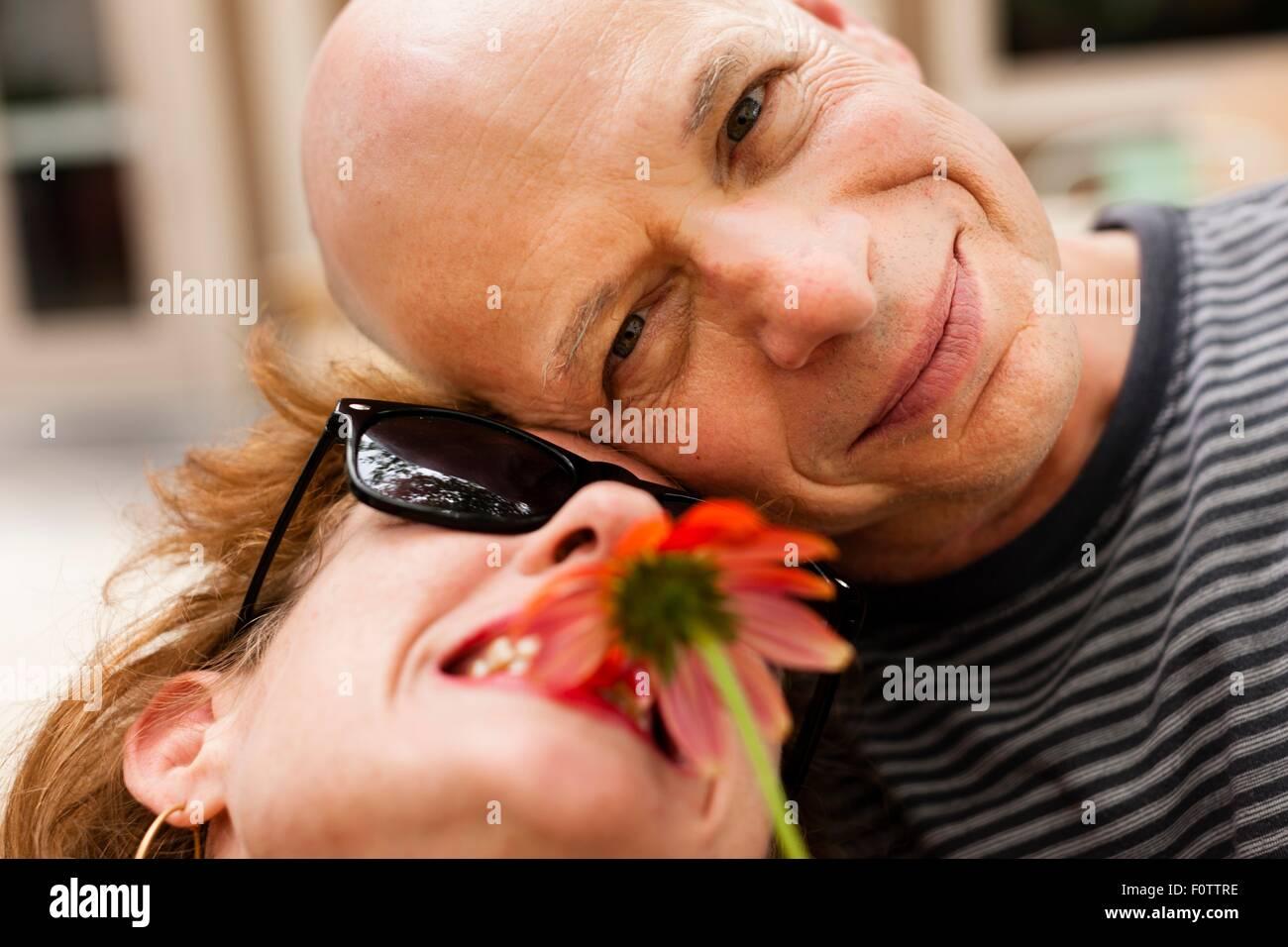 Close up portrait of smiling couple avec fleur rouge Banque D'Images
