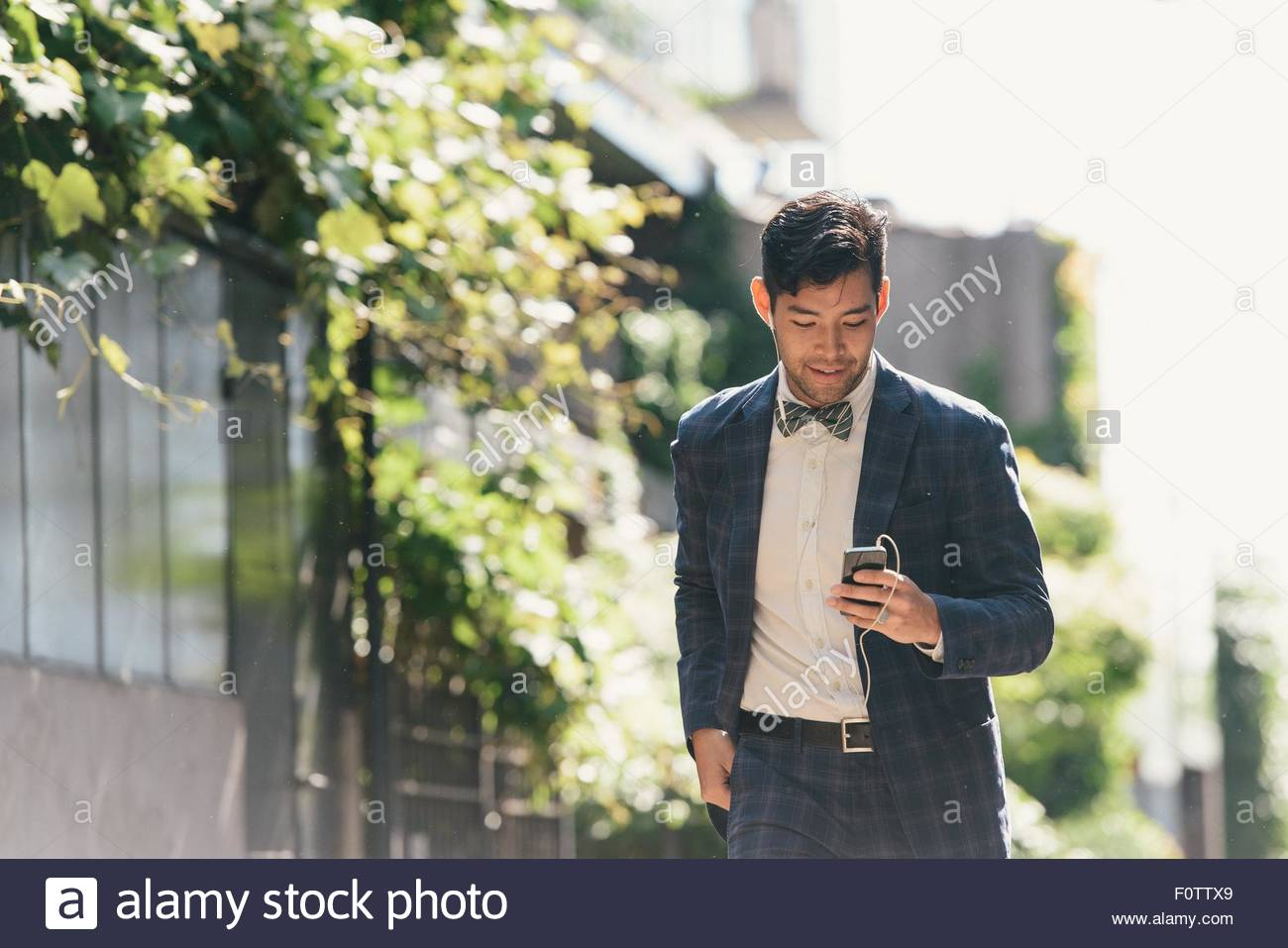 Classy businessman choisir musique smartphone, West Village, Manhattan, USA Photo Stock