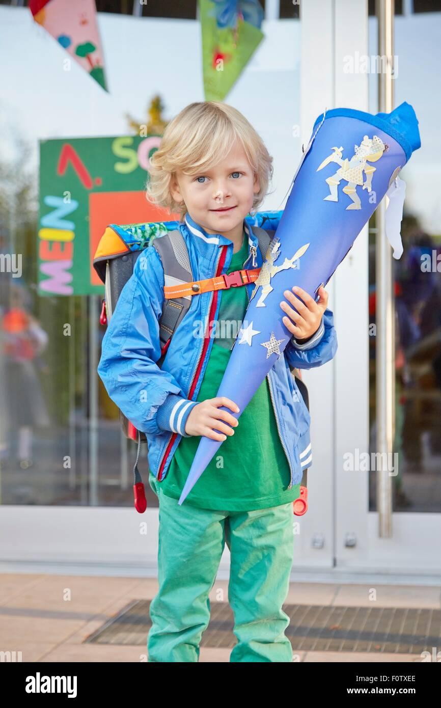 Portrait de jeune garçon au premier jour d'école, holding school cone, Bavière, Allemagne Photo Stock