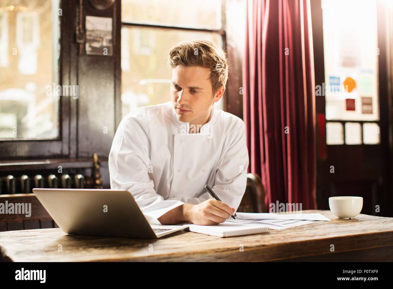 Jeune homme portant uniforme chef using laptop Photo Stock