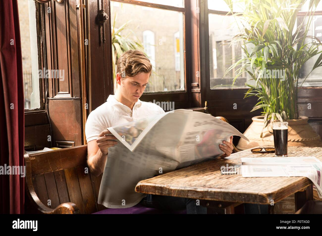 Young man sitting at table reading newspaper Photo Stock