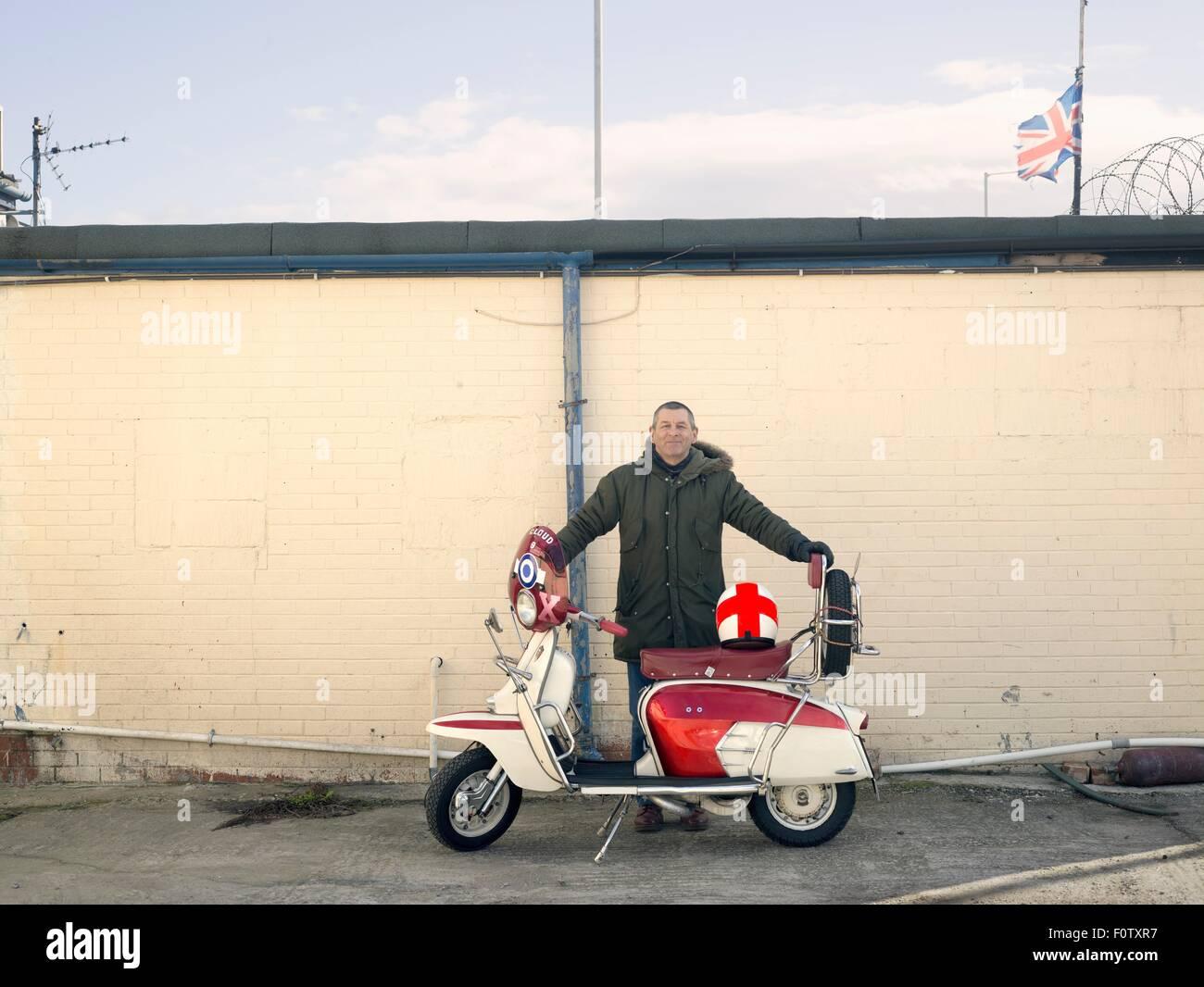 Portrait de mâle mature mod avec un cyclomoteur en face de wall Photo Stock
