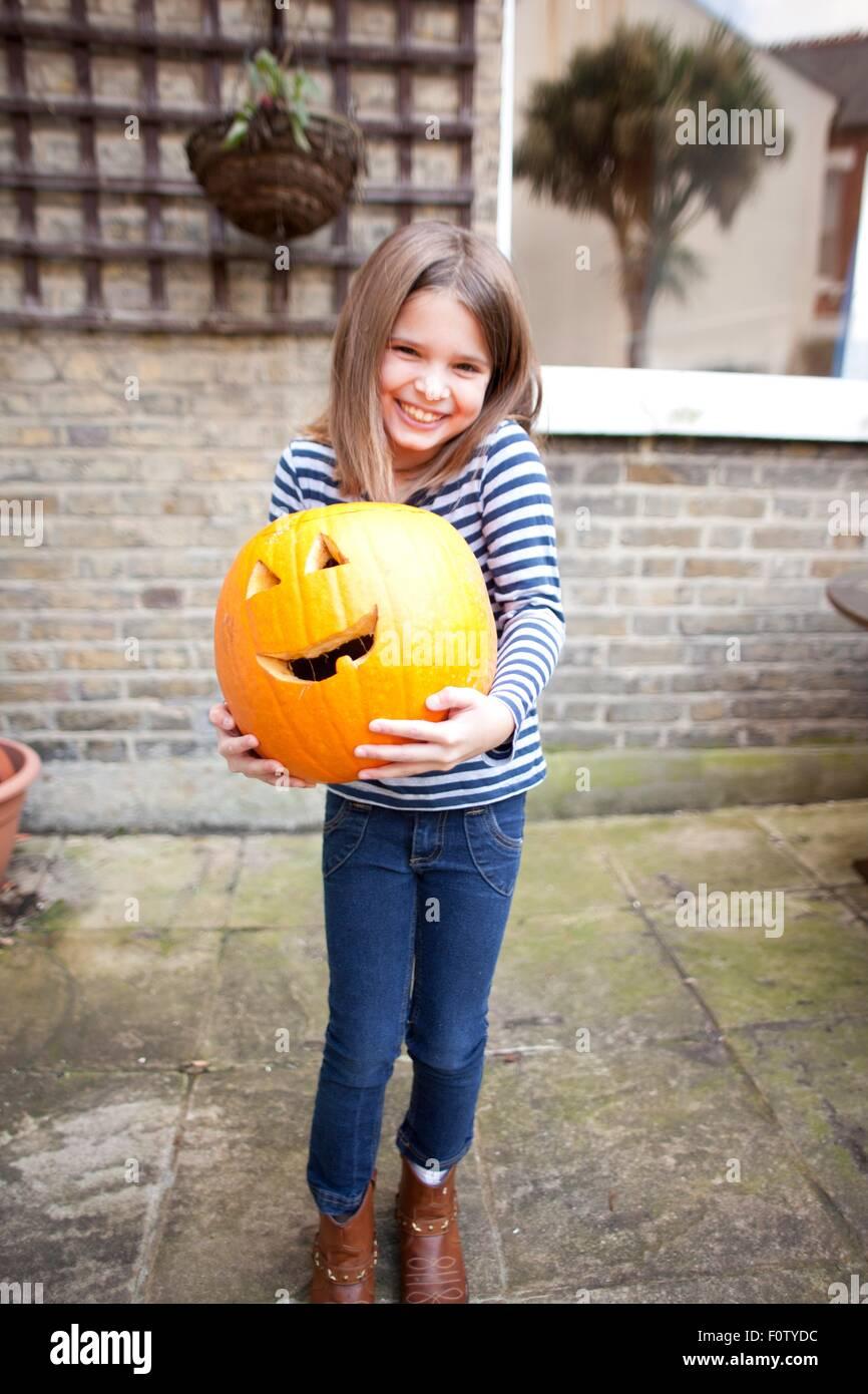 Smiling girl holding heavy halloween citrouille dans jardin Photo Stock