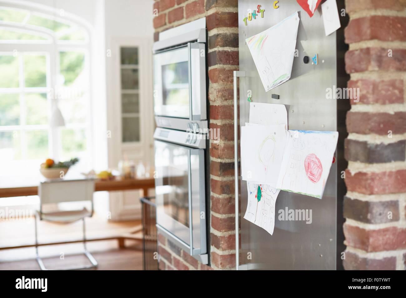 Des dessins d'enfants coincés sur porte de réfrigérateur Photo Stock