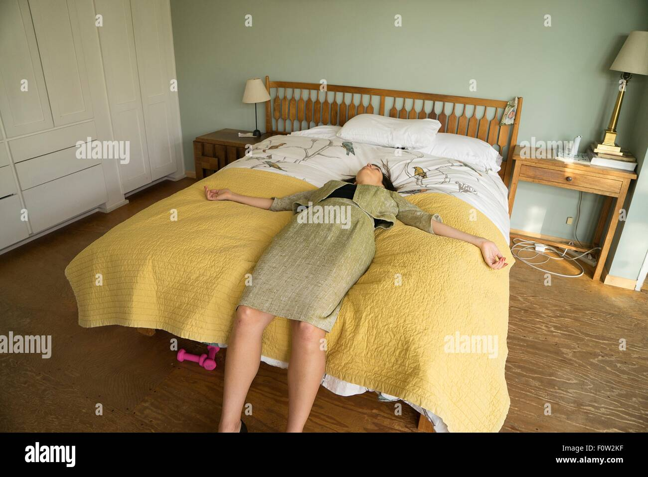 Mid adult woman lying on bed with arms open Banque D'Images