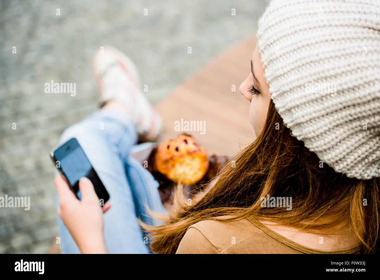 Ado - young woman eating muffin dans la rue et à la recherche dans le téléphone Photo Stock
