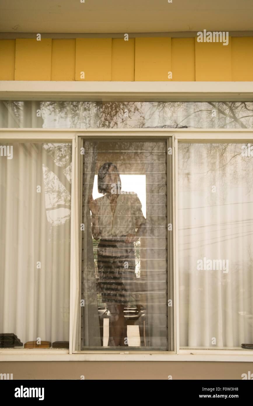 Femme regardant par la fenêtre de la chambre Photo Stock