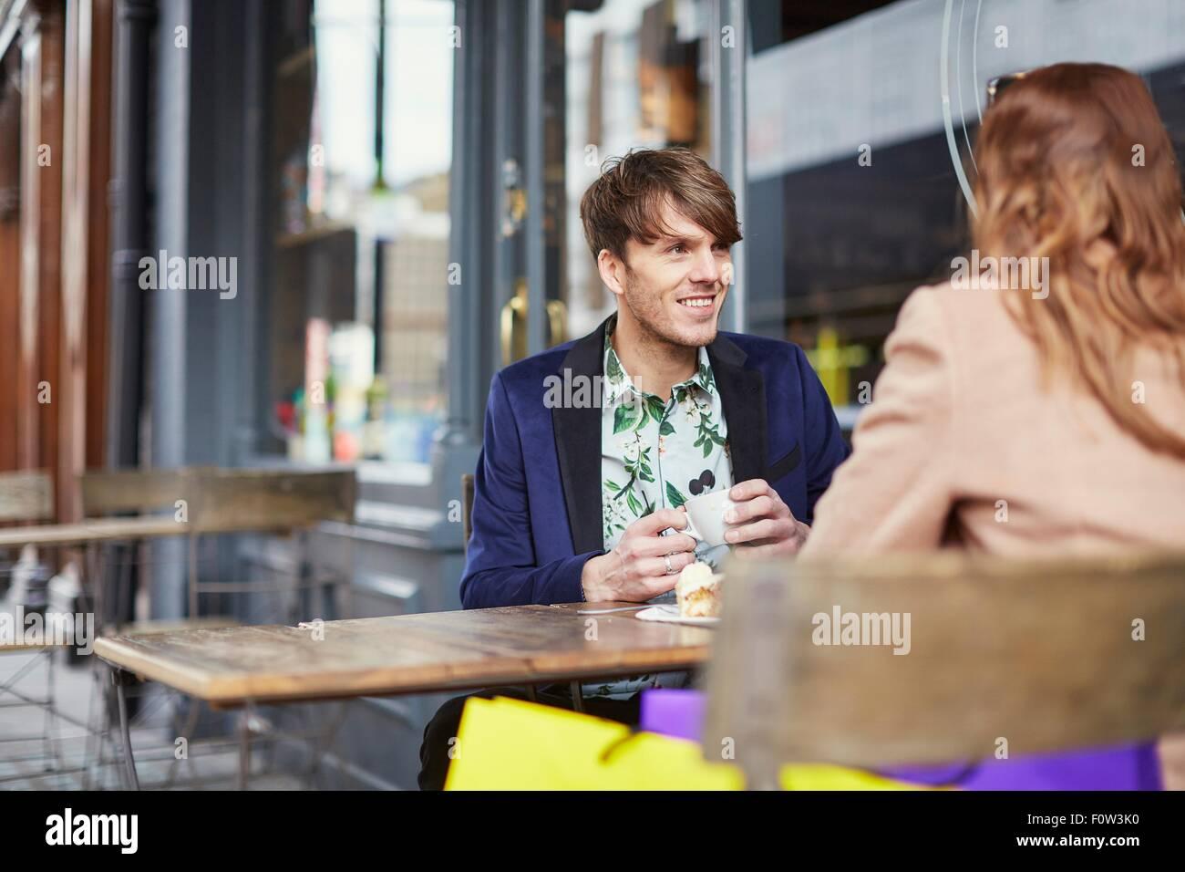 Plus d'épaule de couple chatting at sidewalk cafe, London, UK Banque D'Images