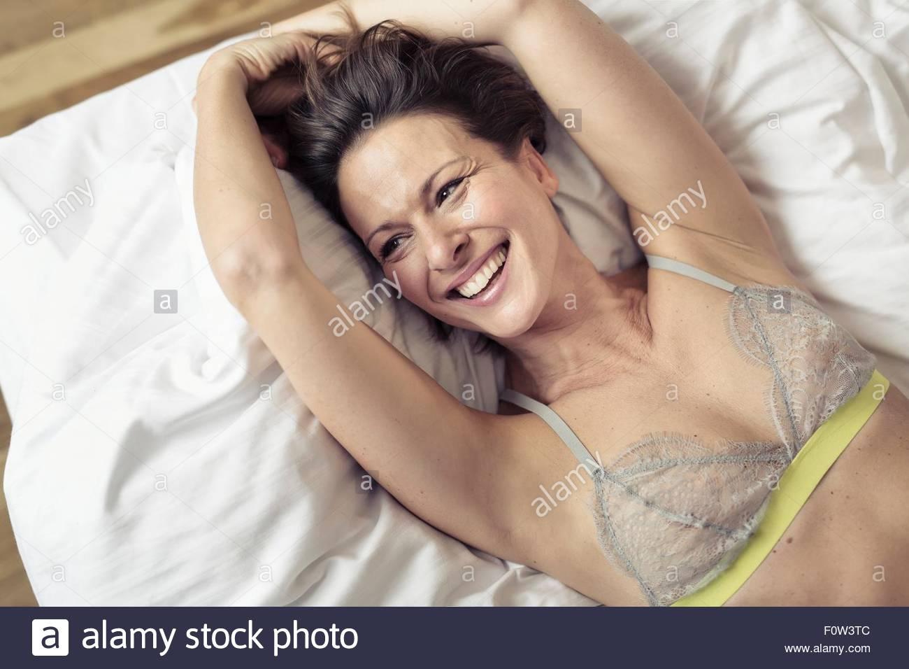 Vue de dessus de soutien-gorge mature woman lying on bed Photo Stock