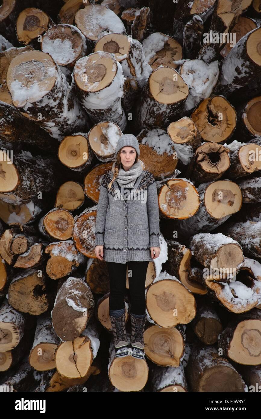 Femme Debout contre la pile de grumes en hiver Photo Stock