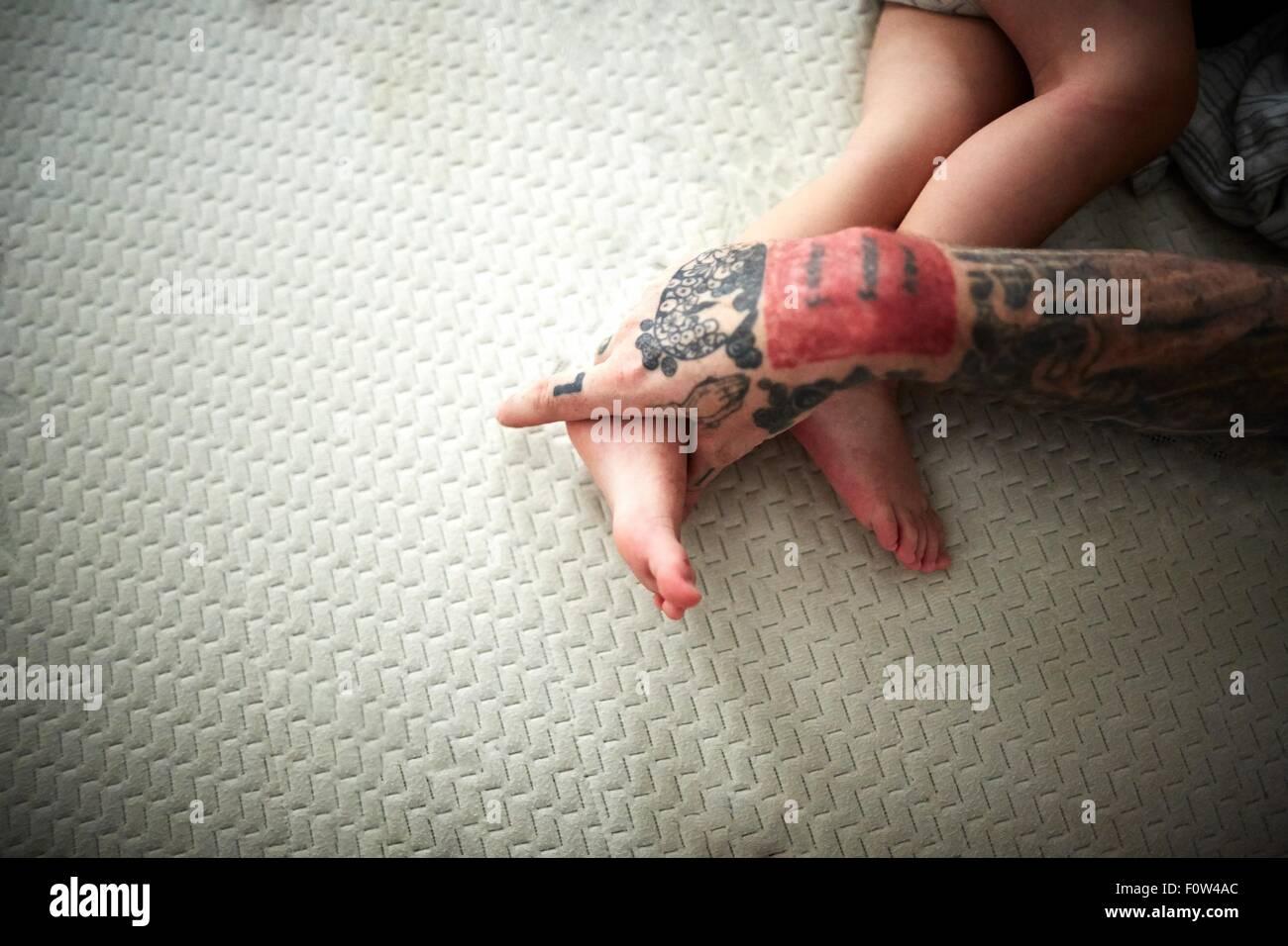 La main tatouée reposant sur des jambes du garçon Photo Stock