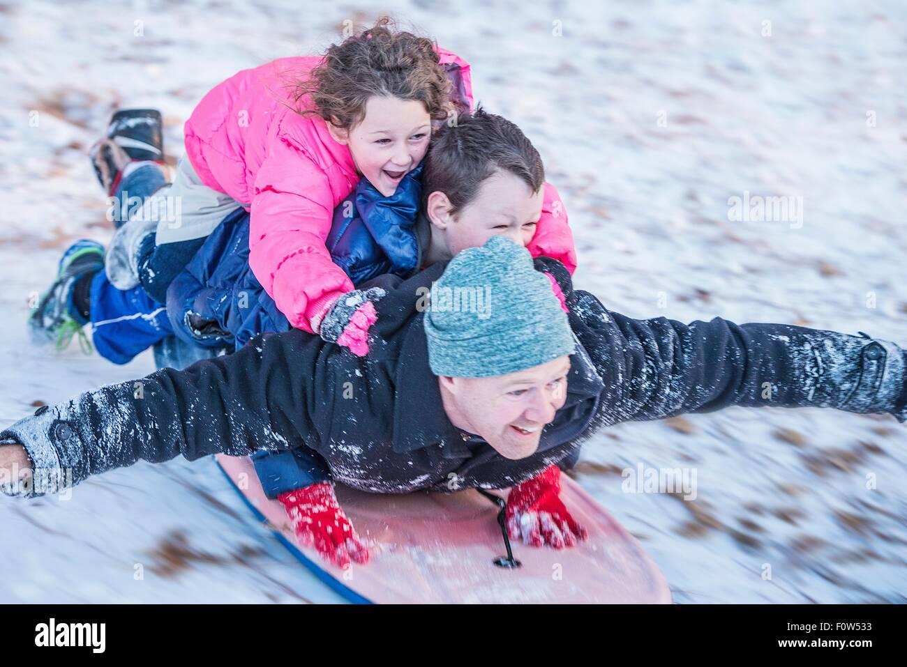 Portrait du père, son fils et sa fille portant sur le dessus de l'autre circonscription en bas de la colline Photo Stock