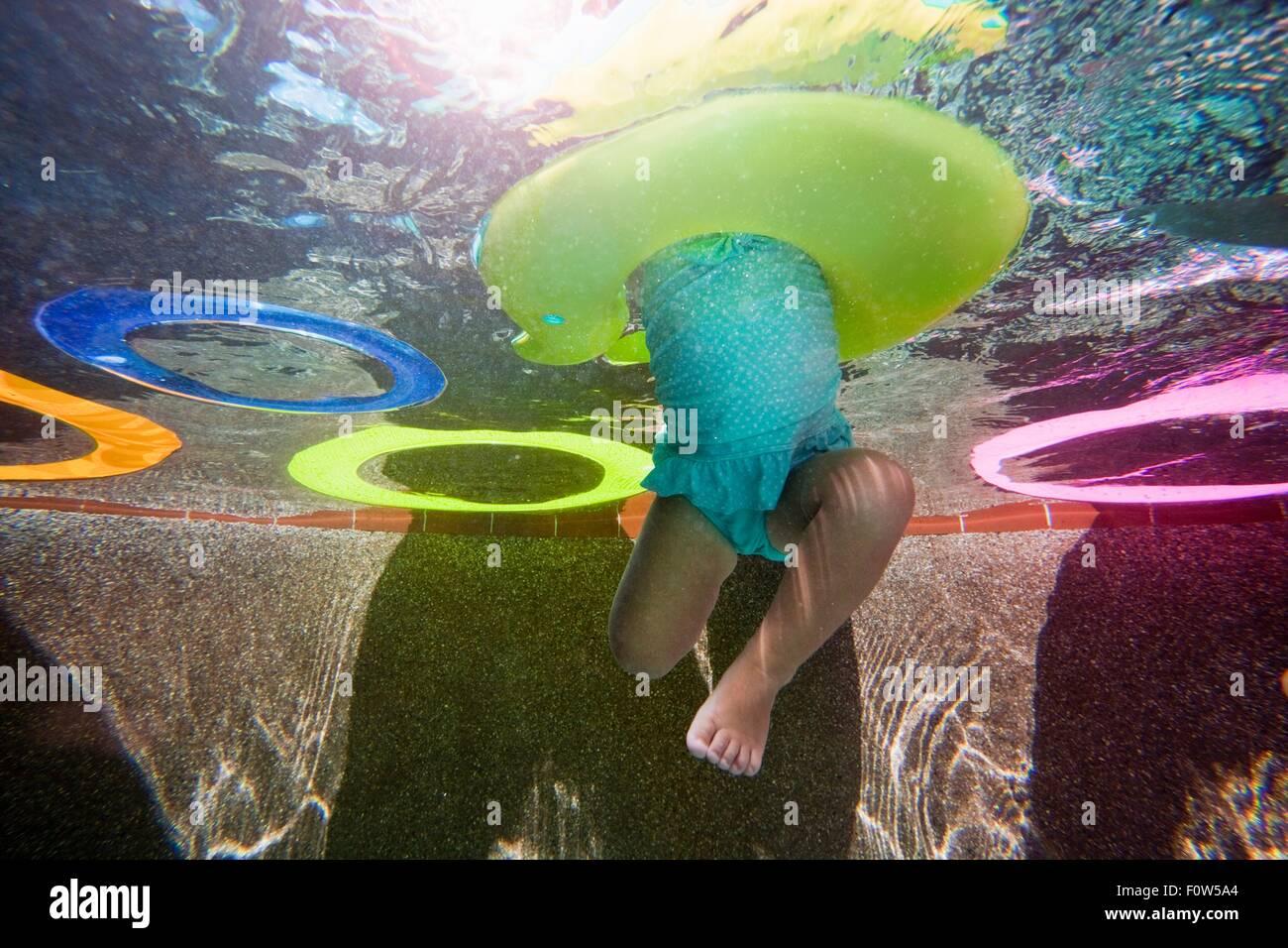 Underwater girl battre des jambes dans la piscine apprendre à nager avec bague en caoutchouc Photo Stock