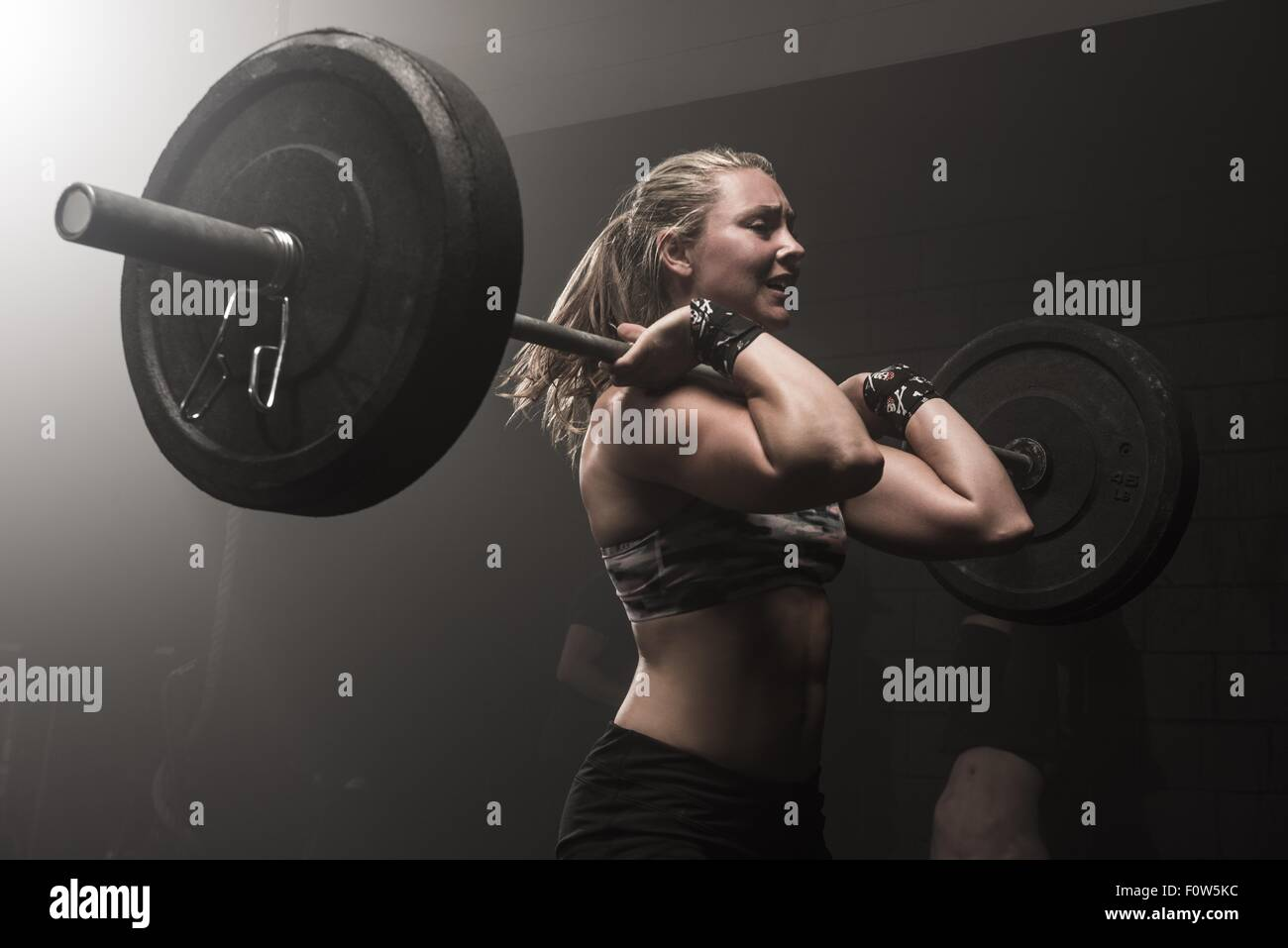 Jeune femme barbell levage Photo Stock