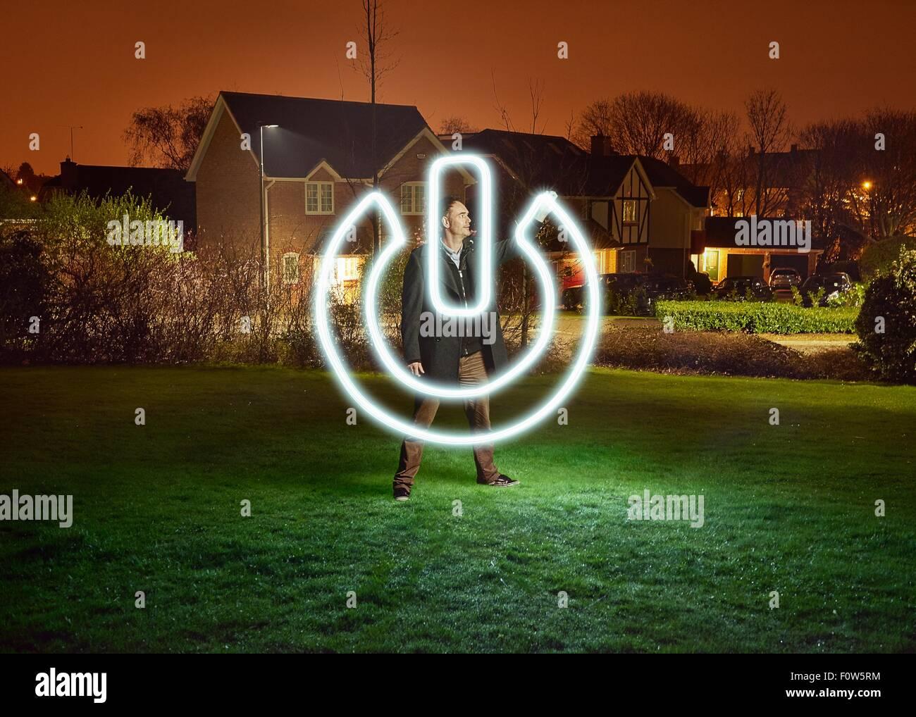 La lumière de l'artiste la peinture d'un interrupteur de symbole dans park Photo Stock