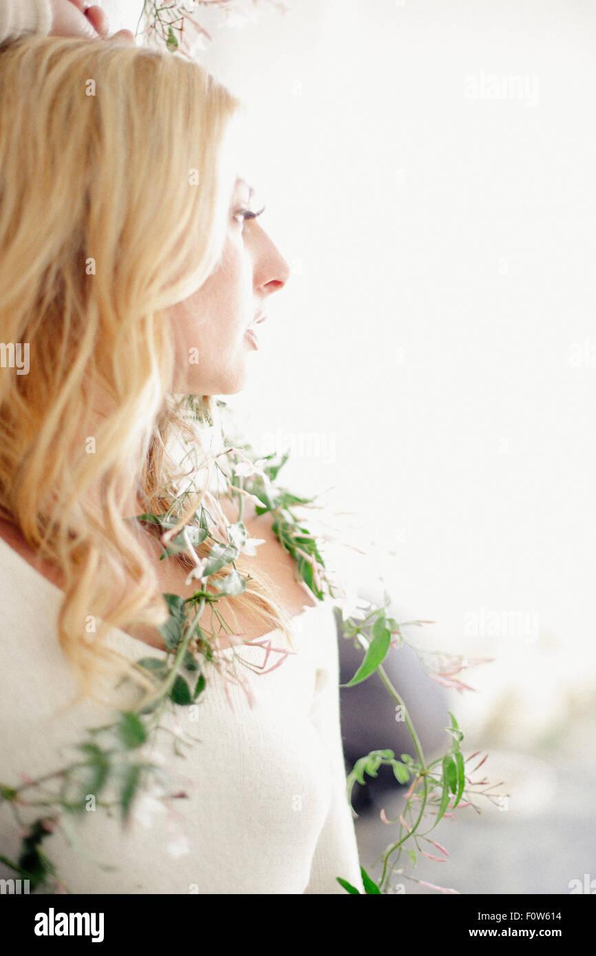 Head and shoulders portrait d'une femme blonde, une plante rampante enroulé autour de son corps. Photo Stock