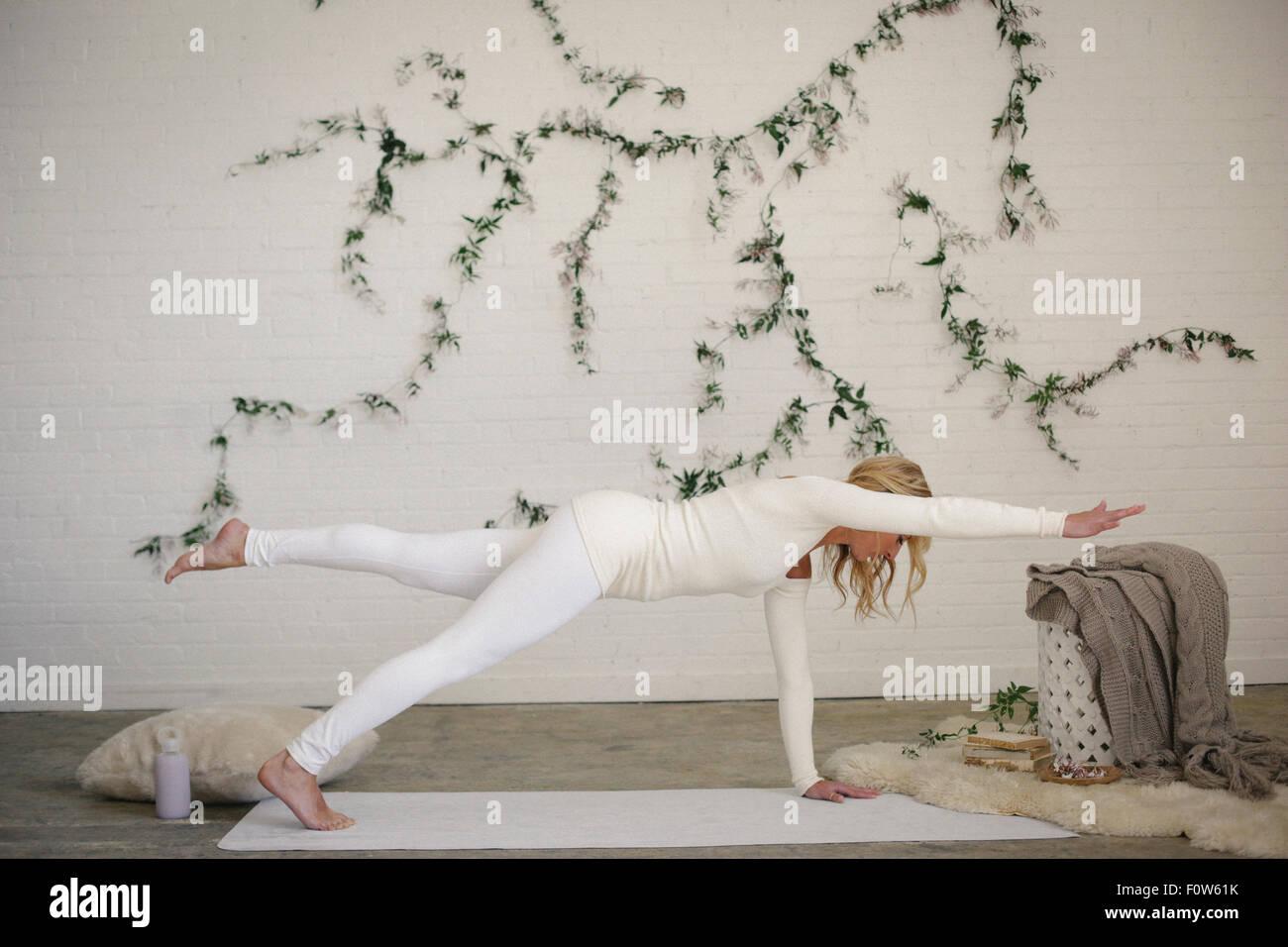 Une femme blonde sur un tapis blanc dans une chambre, sa jambe et bras tendus. Une plante rampante sur le mur derrière Photo Stock
