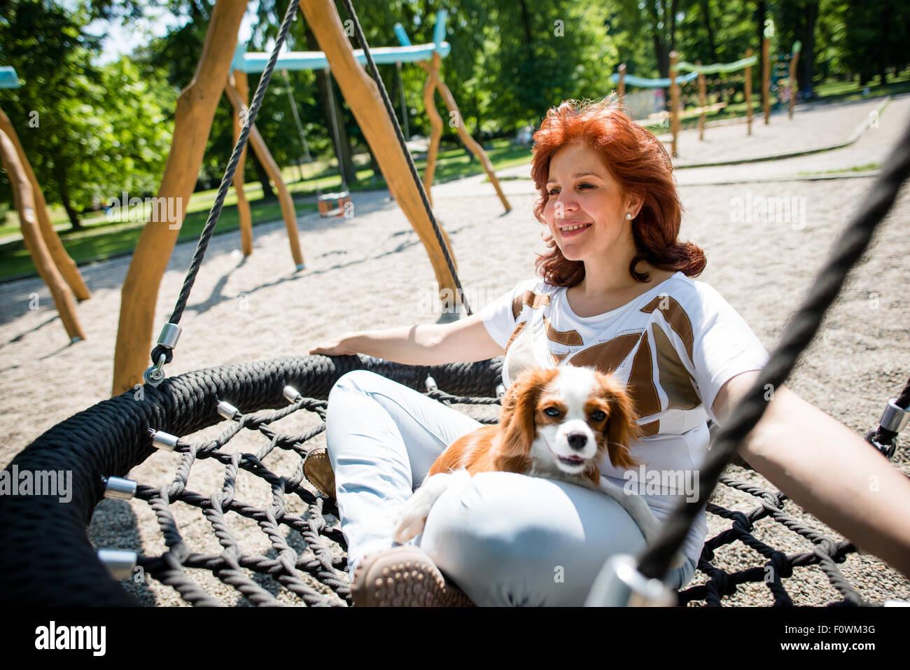 Femme mature se balancer avec son ami des animaux à l'extérieur de jeu pour enfants Photo Stock