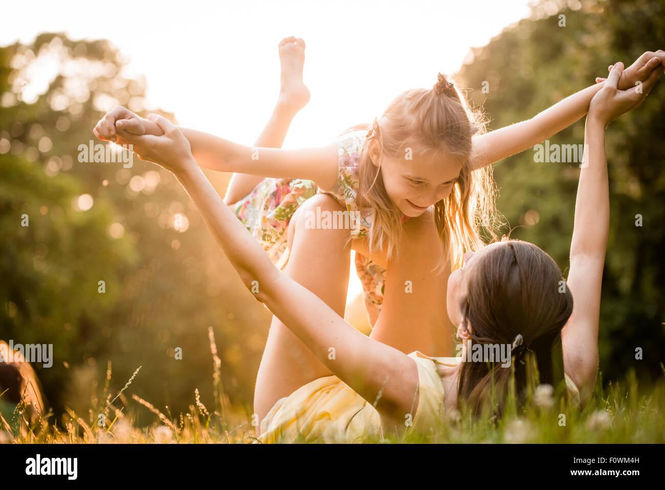 Mère couchée sur l'herbe et joue avec sa fille on airplane Photo Stock