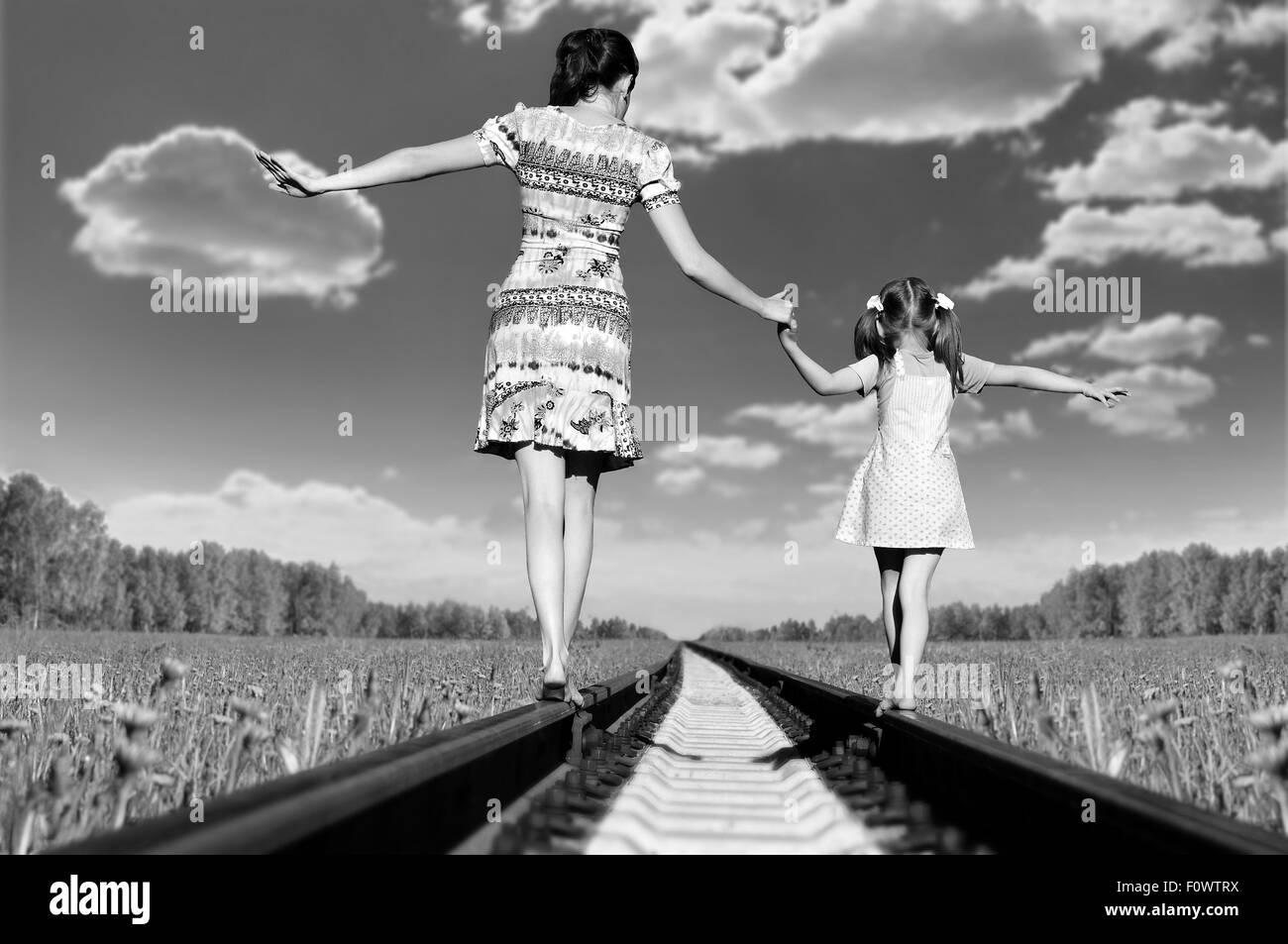 Mère avec la fille, rendez-vous sur rails, un retour à une caméra, dans le champ, à l'été Photo Stock