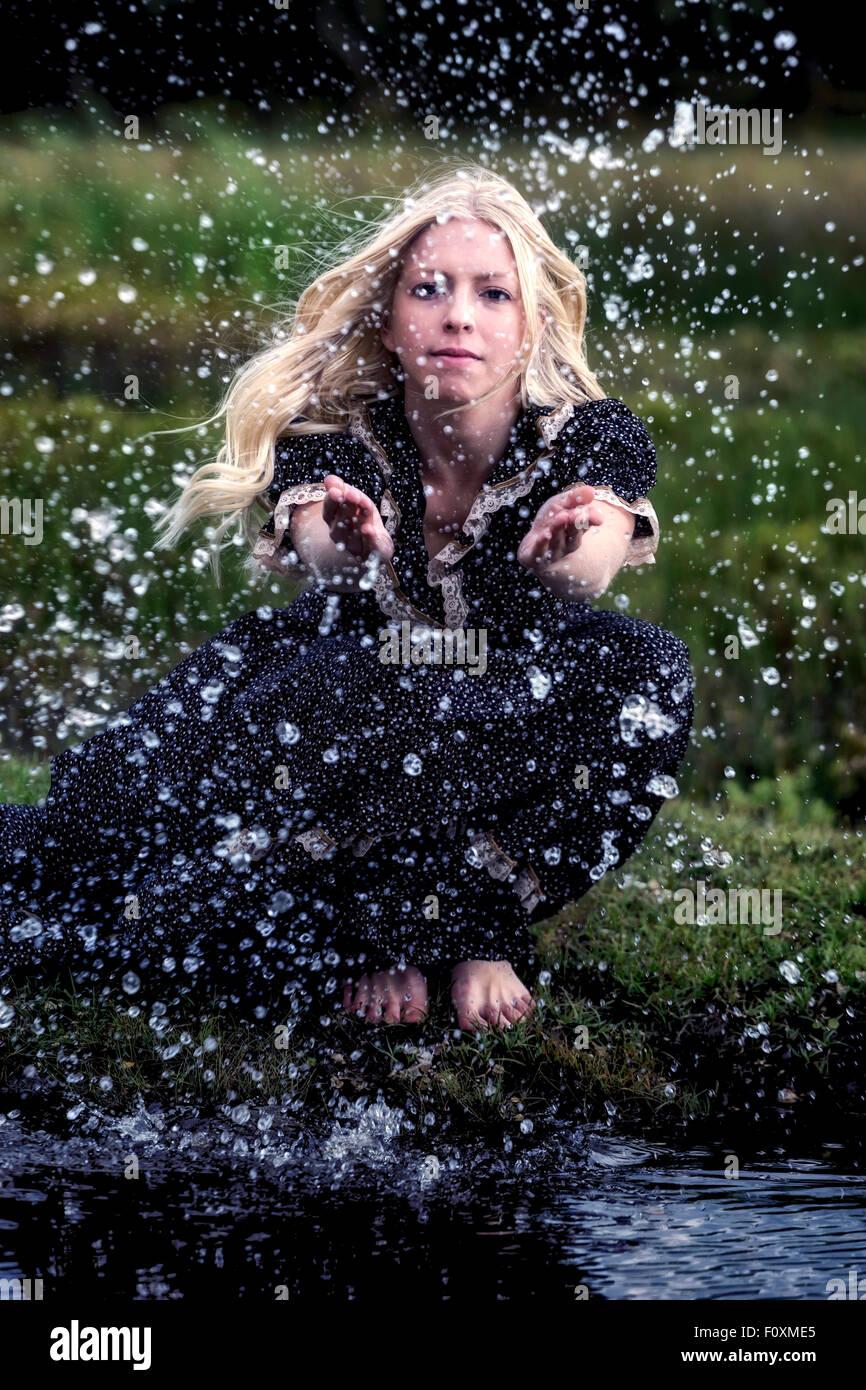 Une femme est assise à un étang et est la projection avec de l'eau Photo Stock