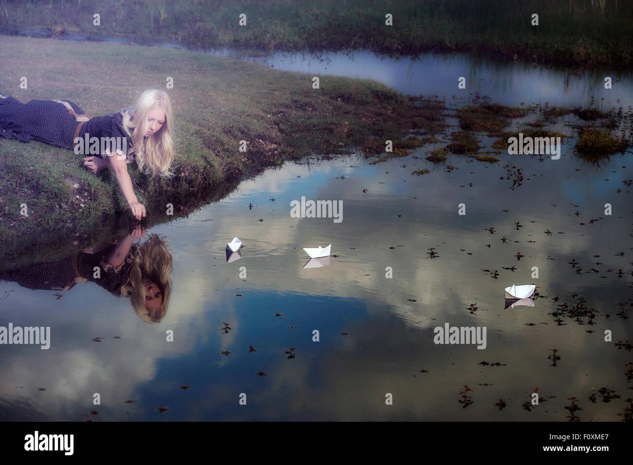 Une fille avec trois bateaux en papier sur un étang Photo Stock