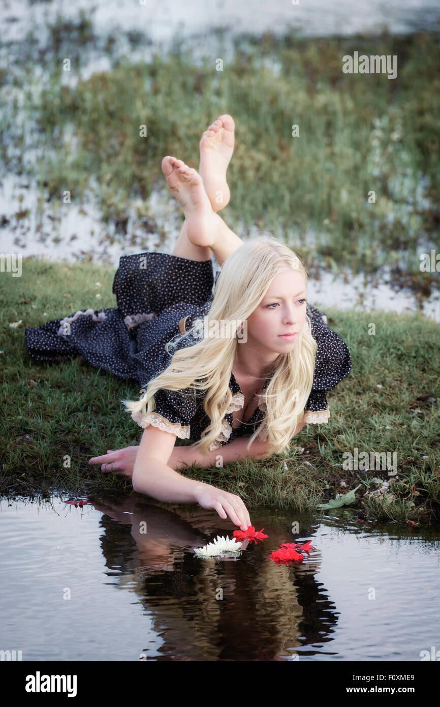 Une fille blonde est de placer des fleurs sur un étang Photo Stock