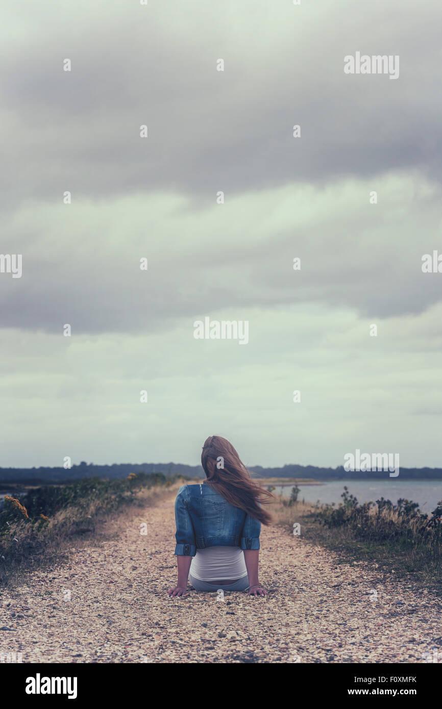 Une femme est assise sur un chemin à la côte Photo Stock