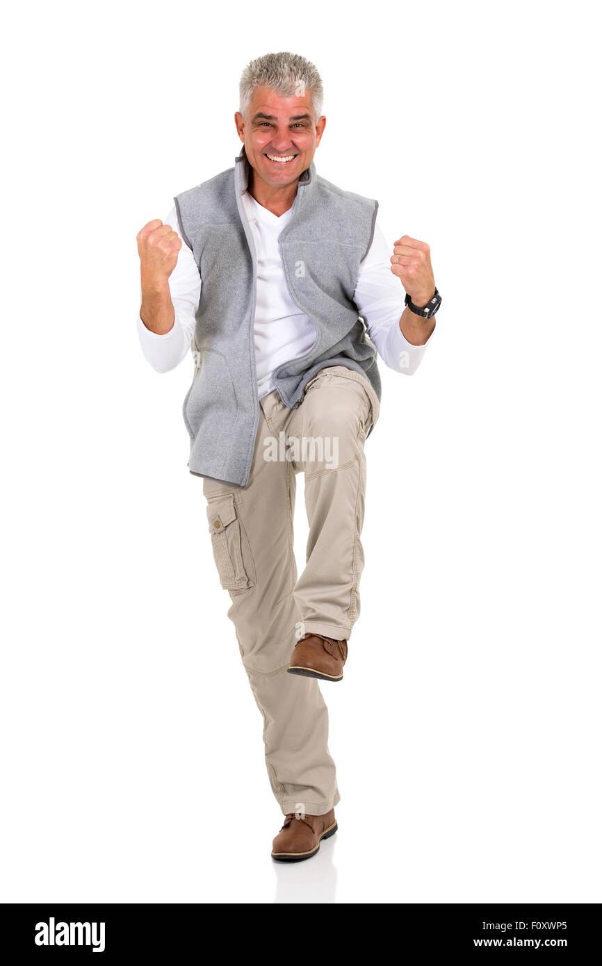 Homme d'âge moyen excité maintenant poings sur fond blanc Photo Stock