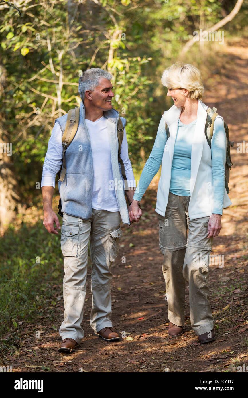 L'âge moyen d'amour couple en train de marcher dans la forêt et tenir la main Photo Stock