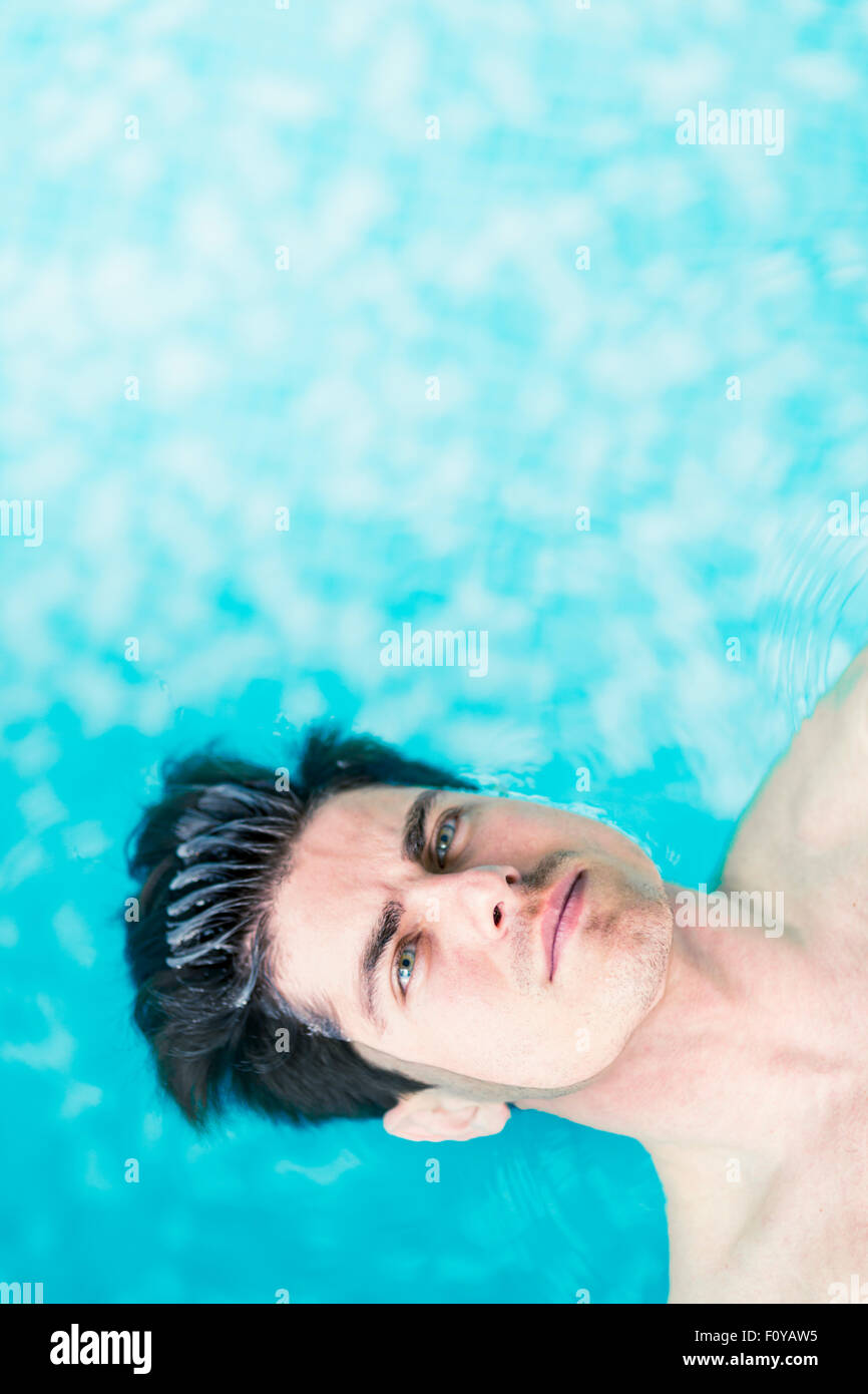 Portrait d'un bel homme flottant à la surface de l'eau Photo Stock