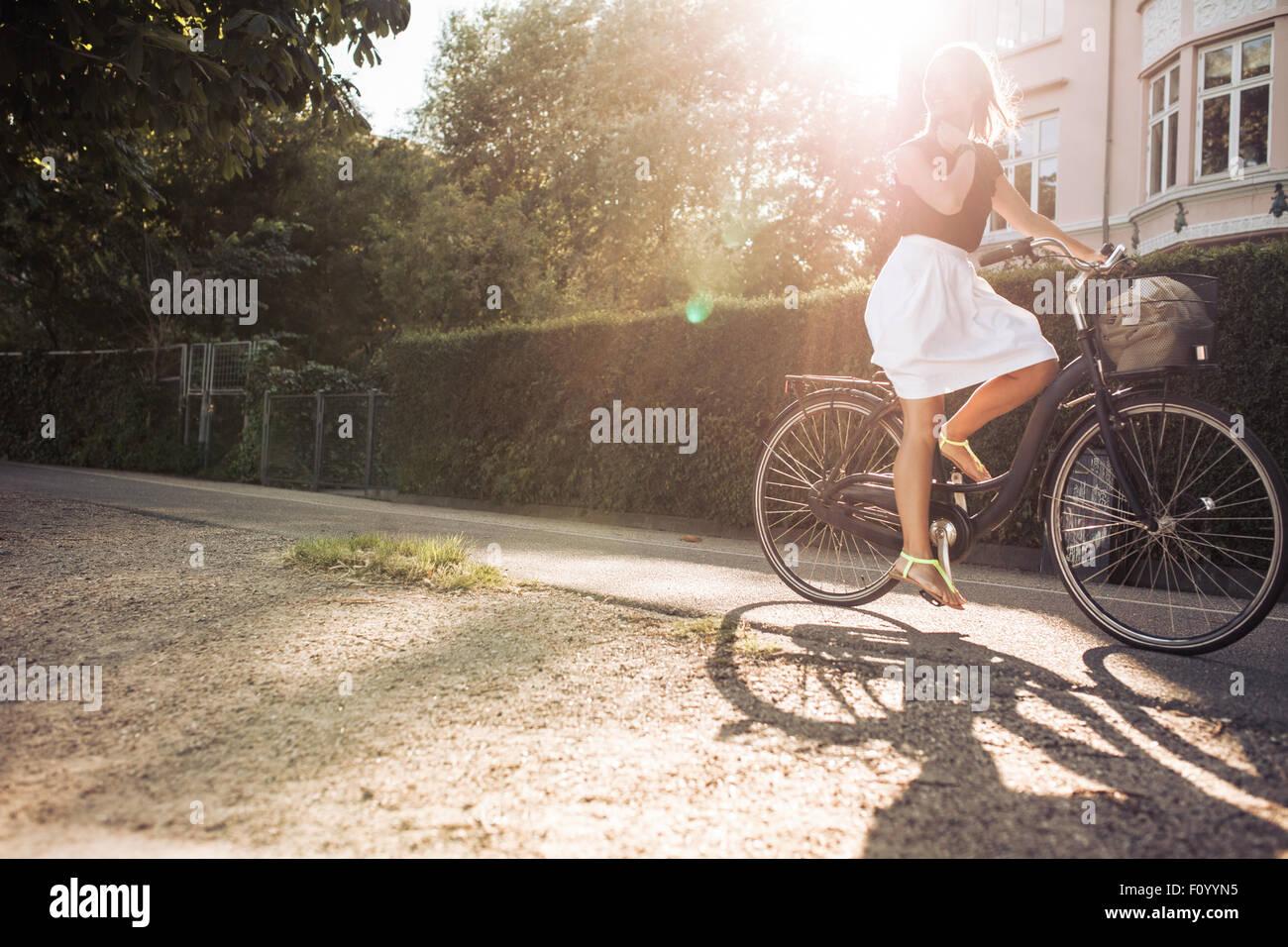Tourné en plein air d'une jeune femme à vélo sur rue. La femme location avec sun flare. Photo Stock