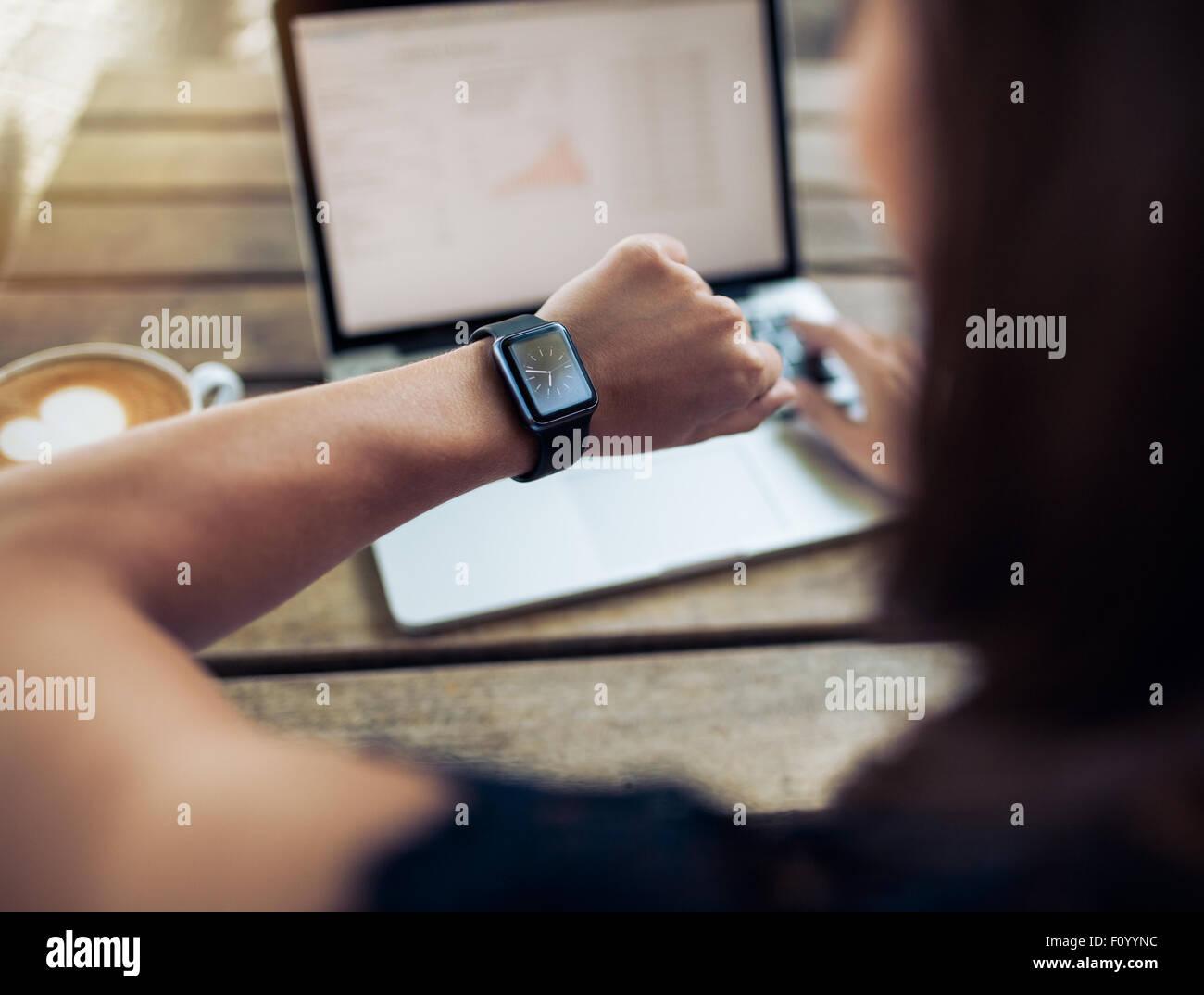 Gros plan d'une femme de vérifier de temps à sa smartwatch. Femme assise dans un café avec un Photo Stock