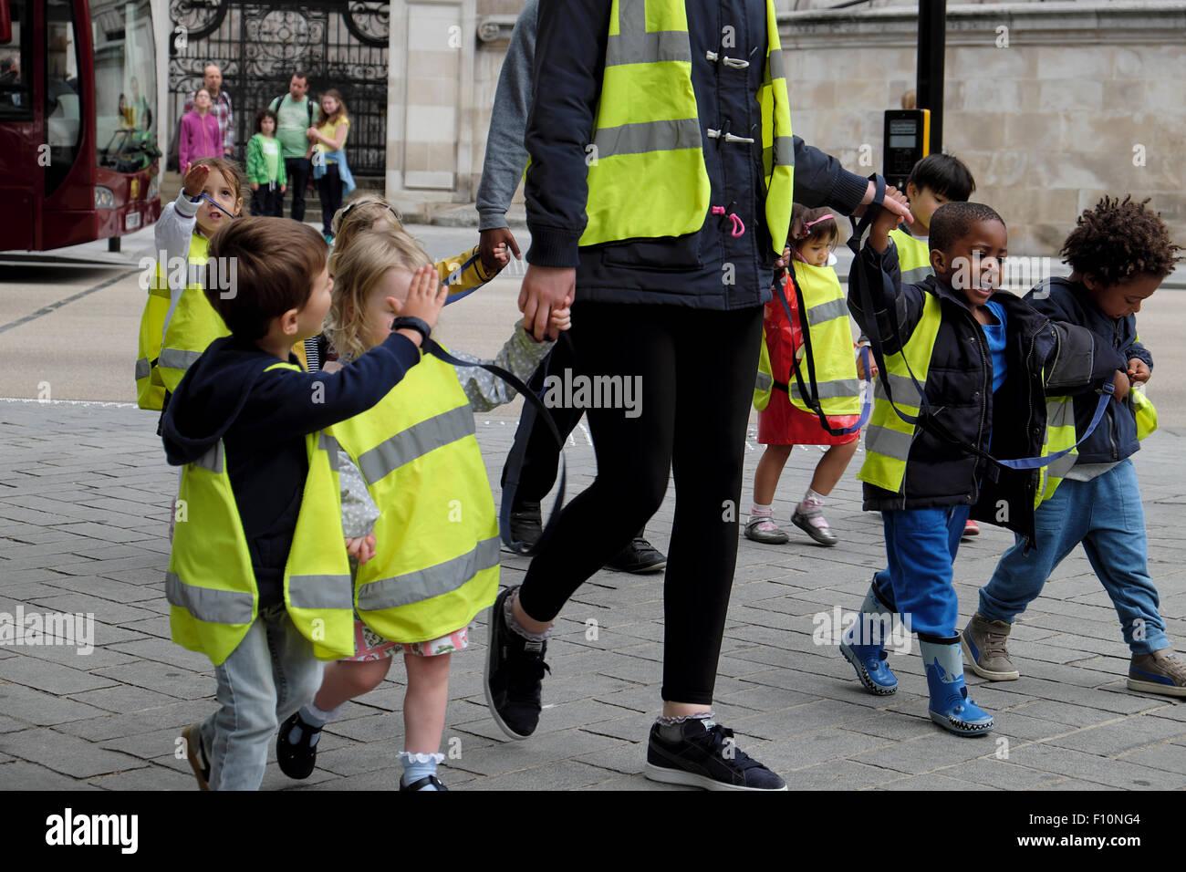 Les enfants d'école maternelle & nourrice portant des vestes de sécurité fluorescent haute visibilité tenir la main sur marche dans une rue de Londres UK KATHY DEWITT Banque D'Images