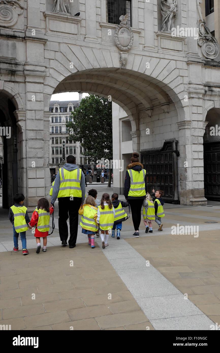 Les enfants d'école maternelle & assistantes maternelles portant des vestes de sécurité fluorescent haute visibilité tenir la main sur marche dans une rue de Londres UK KATHY DEWITT Banque D'Images