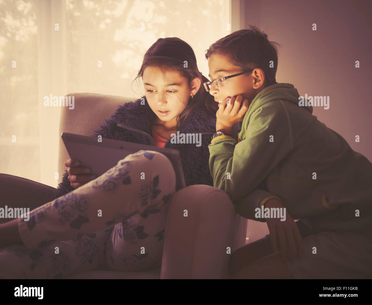 Mixed Race children using digital tablet in living room Banque D'Images