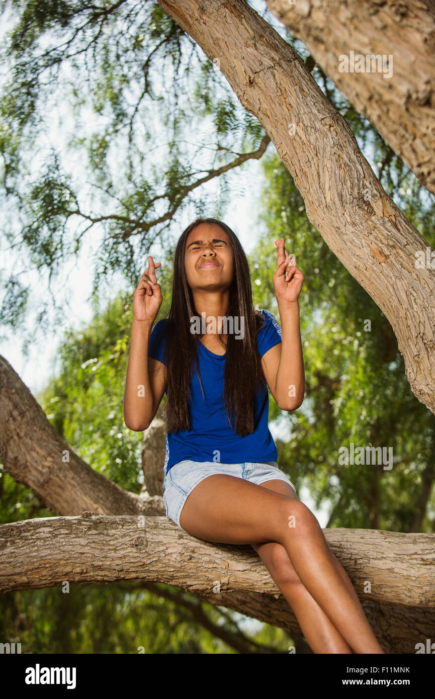Mixed Race girl crossing fingers on tree branch Banque D'Images