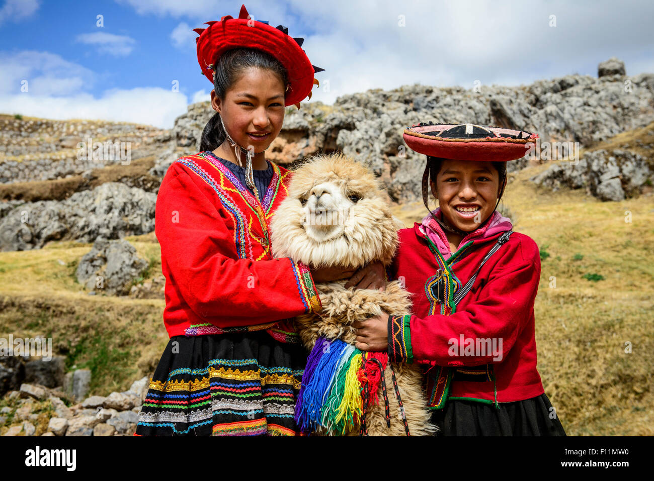 Hispanic sisters smiling with llama in rural landscape Photo Stock
