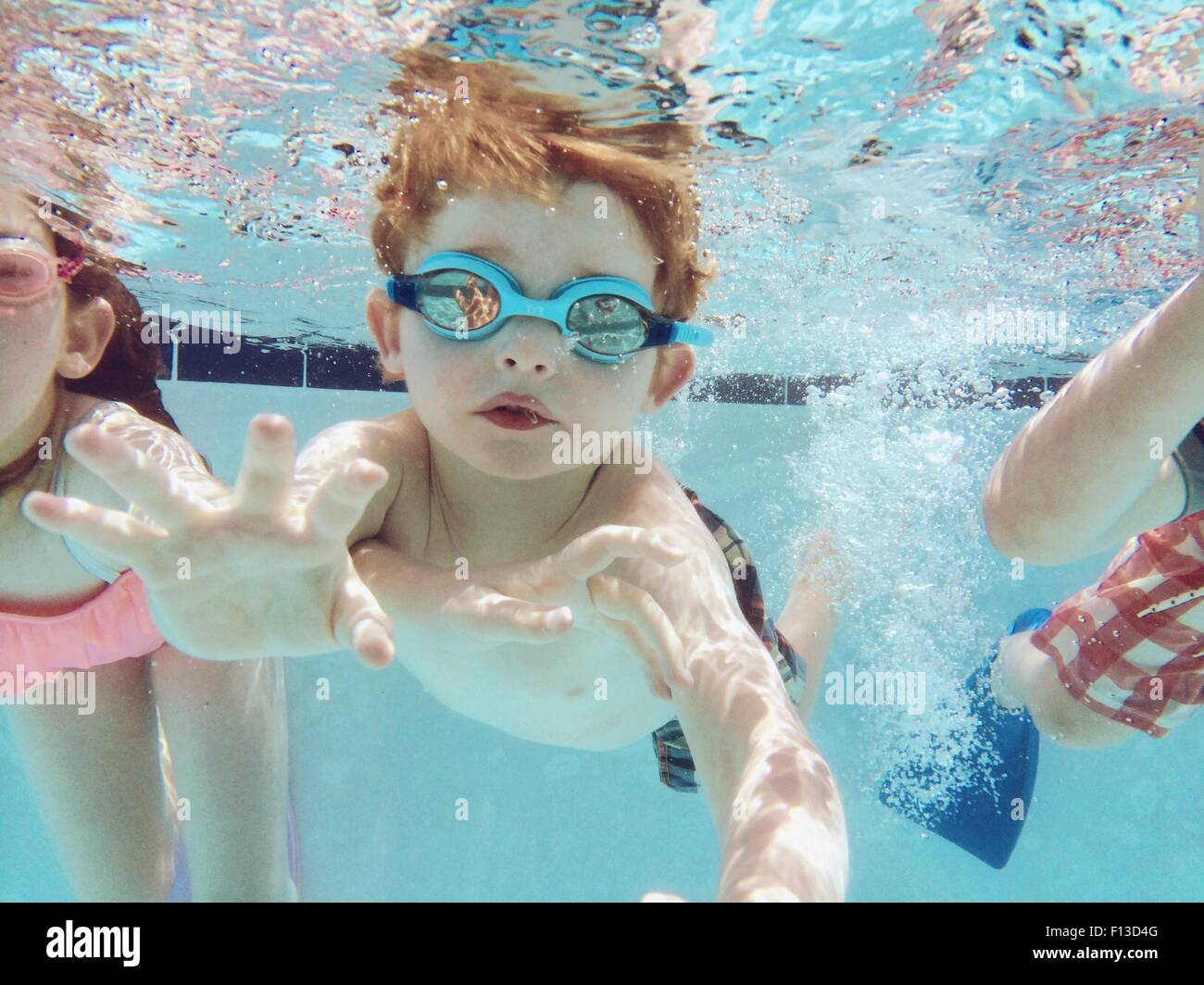 Portrait of a Boy swimming underwater avec des amis Photo Stock