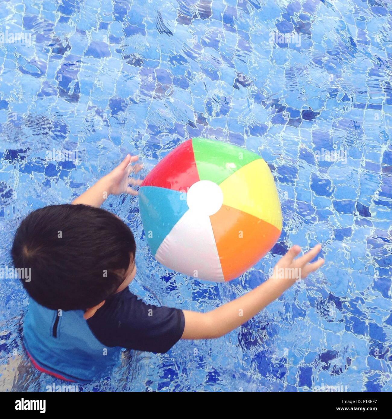 Vue aérienne d'un garçon jouant avec un ballon de plage dans la piscine Photo Stock