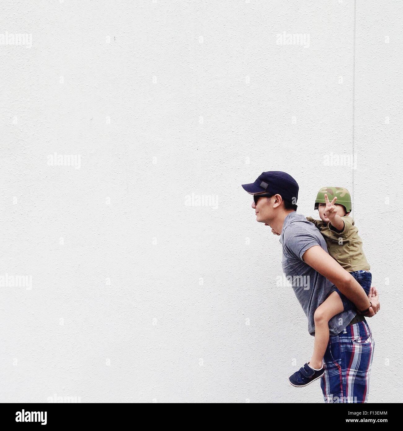 Père de donner son fils un piggyback ride Photo Stock