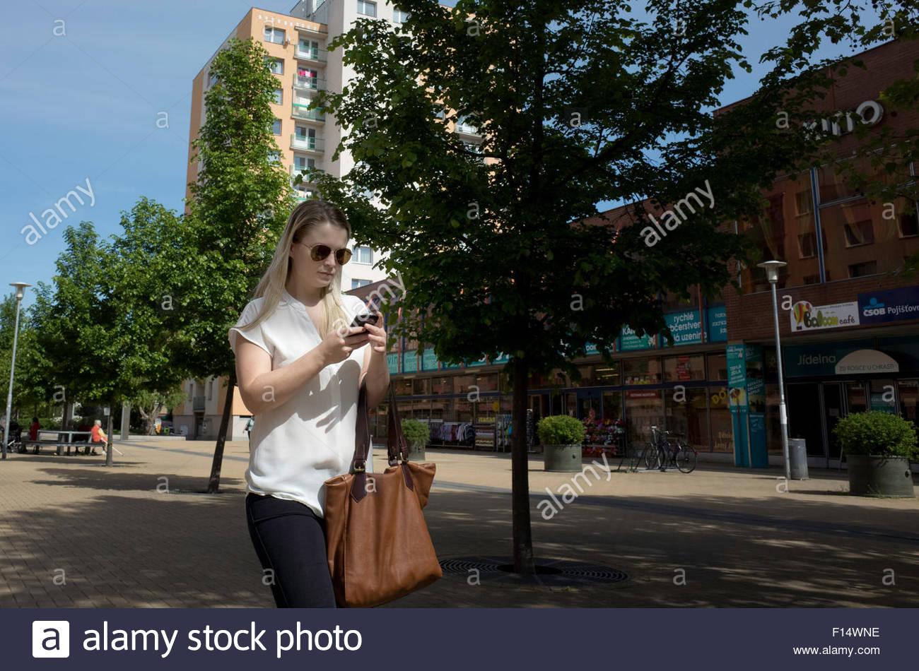 Blonde femme marche et navigation sur Internet sur son smartphone Photo Stock