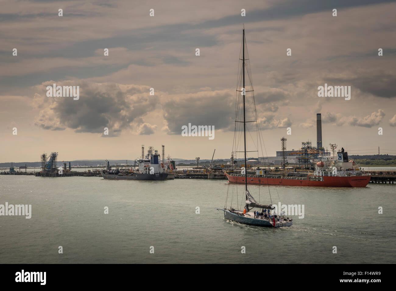 Un yacht à passant de pétroliers à quai à la raffinerie de pétrole de Fawley près de Southampton, Hampshire, Royaume-Uni Banque D'Images