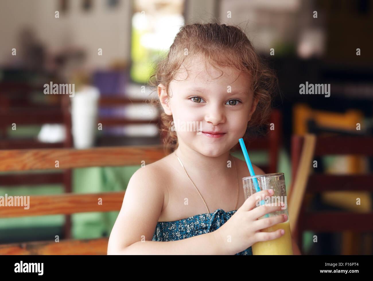 Happy smiling kid girl drinking jus frais à partir de café en verre Photo Stock