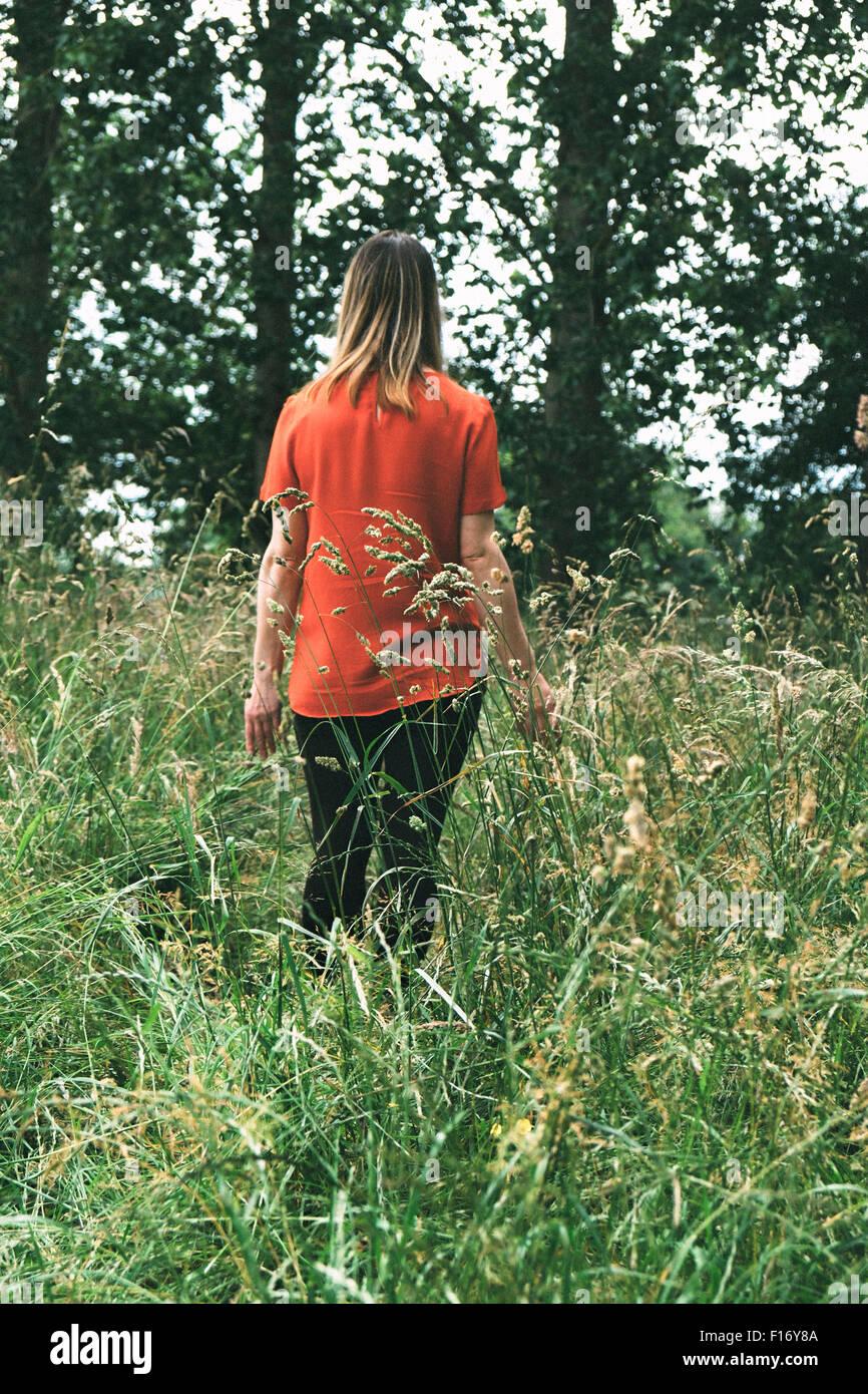 Femme marche à travers un champ d'herbe haute Photo Stock